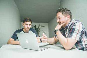 מורה פרטי לאנגלית מלמד נער עם מחשב נייד אפל