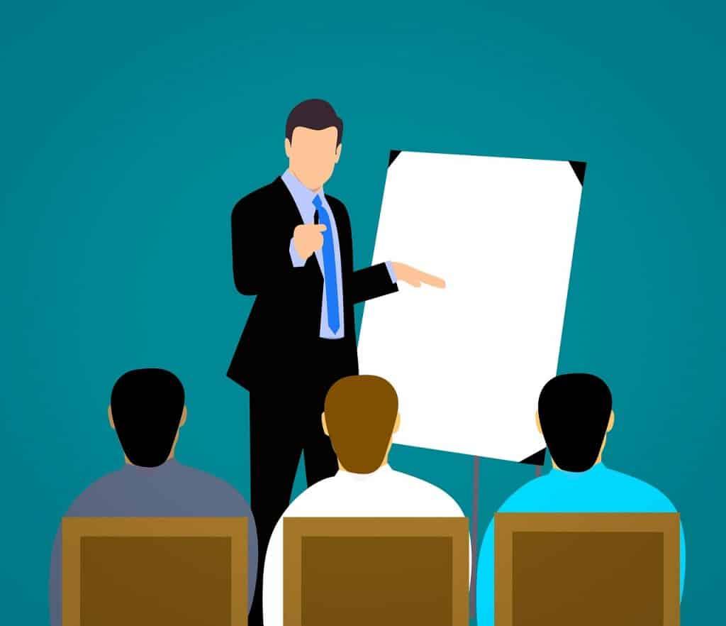 מורה לאנגלית עסקית בחליפה מעביר שיעור לשלושה תלמידים